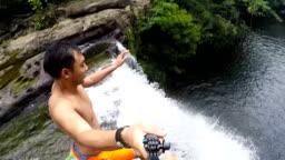 Extremely High POV Cliff Jump into Water above Waterfall Trees and Rocks Below on a Beautiful Sunny Day in Summer in the Forest with a Thumbs Up to Bystanders Extreme Fun Point of View Head Camera