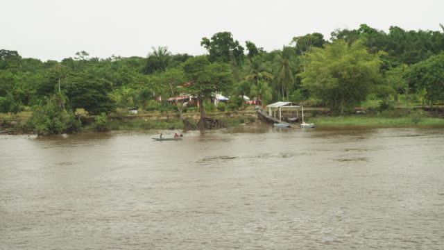 vidéos et rushes de extremely wide shot of fishing village on the river bank surrounded by jungle - village
