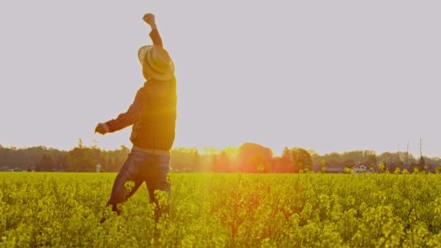 vidéos et rushes de exubérant agriculteur sautant et les acclamations dans le champ de canola jaune rural ensoleillé, idyllique, slow motion - un seul homme d'âge moyen