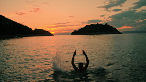 ms exuberant man jumping out of tranquil ocean at sunset,peljesac,croatia - emergence stock videos & royalty-free footage