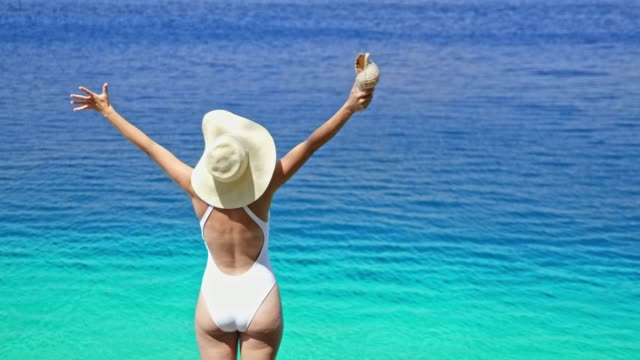 exuberant woman in bathing suit with seashell at sunny summer blue ocean - seashell stock videos & royalty-free footage