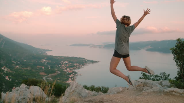 ms exuberant woman jumping for joy at scenic overlook,peljesac,croatia - arms raised stock videos & royalty-free footage