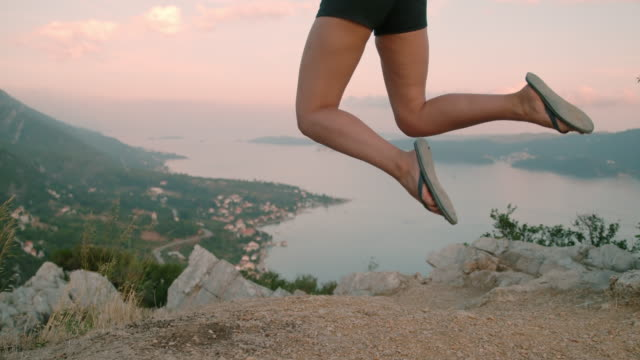 ms exuberant woman jumping for joy at scenic overlook,peljesac,croatia - sandal stock videos and b-roll footage