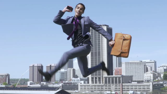 exuberant young businessman jumping while talking on a mobile phone - 書類鞄点の映像素材/bロール