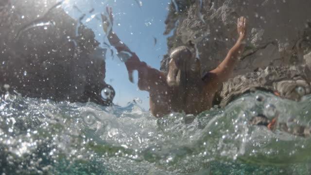 日当たりの良い海、アドリア海、クロアチアから飛び出すms活気に満ちた若い女性 - 水中カメラ点の映像素材/bロール