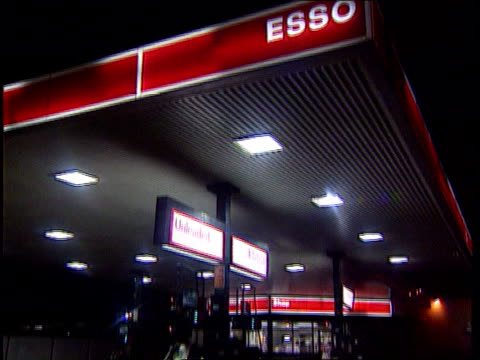 exxon/mobil merger exxon/mobil merger itn london esso garage tilt man filling car at petrol pumps - exxon stock videos & royalty-free footage