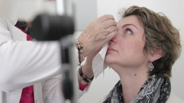 vídeos de stock e filmes b-roll de eye doctor applying eyedropper - cabeça humana