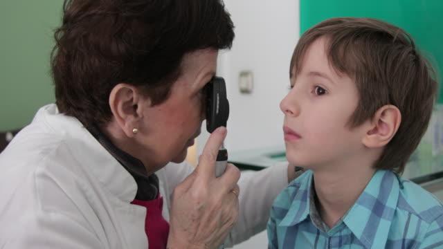 Eye doctor examing little boy eye