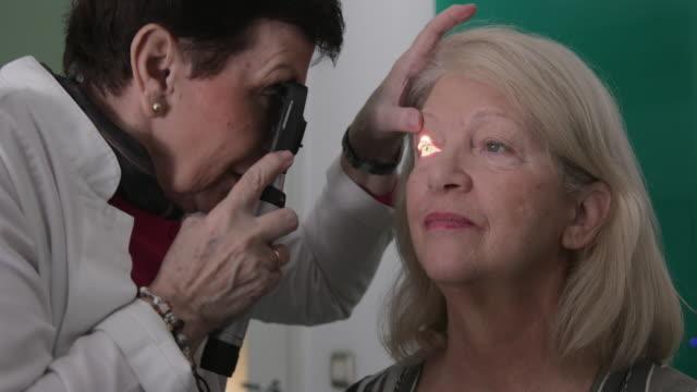 Eye doctor looking into patient eye
