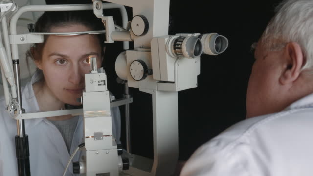 eye exam with a slit lamp. young woman examining eyes at ophthalmologist. white collar workers. active seniors at their work place. - lens optical instrument stock videos & royalty-free footage