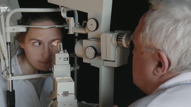 stockvideo's en b-roll-footage met oogonderzoek met een spleetlamp. jonge vrouw die ogen bij oogarts onderzoekt. bedienden. actieve senioren op hun werkplek. - netvlies