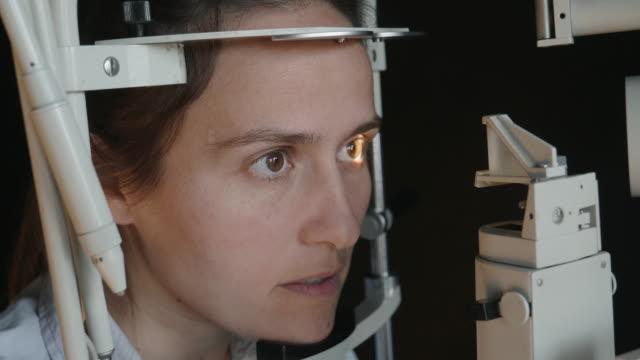 stockvideo's en b-roll-footage met cu, oogonderzoek met een spleetlamp. jonge vrouw die ogen bij oogarts onderzoekt. bedienden. actieve senioren op hun werkplek. - netvlies