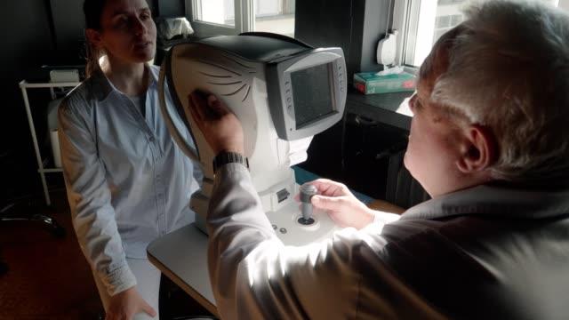 stockvideo's en b-roll-footage met oogonderzoek. jonge vrouw die ogen bij oogarts onderzoekt. bedienden. actieve senioren op hun werkplek. moderne medische apparatuur. - zicht