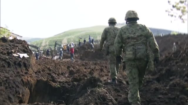eye level view of japanese self defence force crew rescuring and clearing the landslide affected area in minami aso village after consecutive... - 地震点の映像素材/bロール
