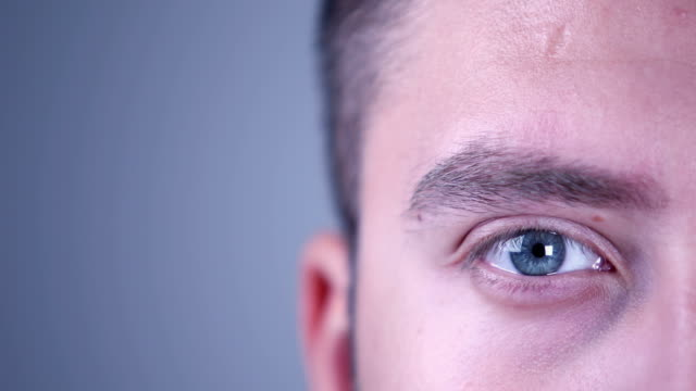 eye of a young man looking at camera - blinking stock videos & royalty-free footage