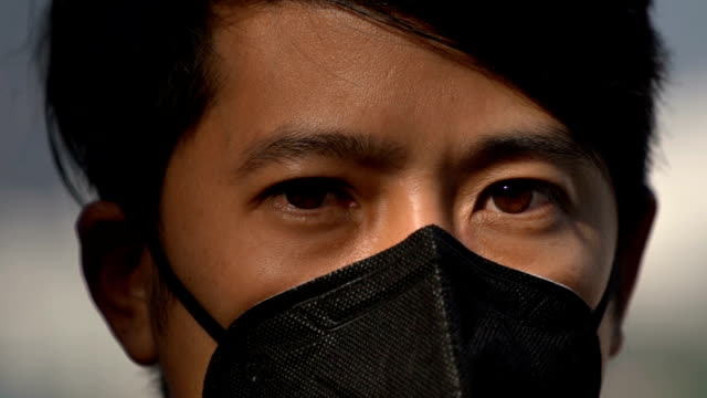 cu slomo - eye shot of asian man with pollution mask - pollution mask stock videos & royalty-free footage