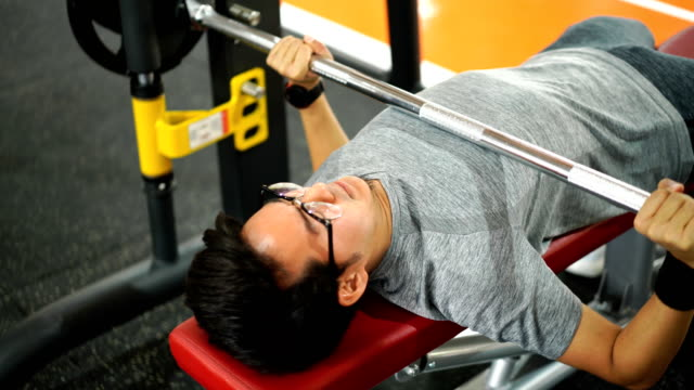 eyeglasses man training with barbell on bench press - bench press stock videos & royalty-free footage