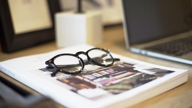 eyeglasses on the magazine with laptop on a wooden table indoors. - spectacles stock videos & royalty-free footage