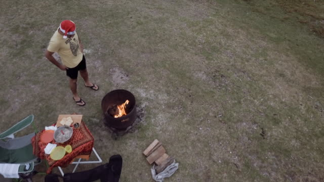 4k eye's bird view of a man camping, with a fire and celebrating christmas, victoria, australia - camping stock videos & royalty-free footage