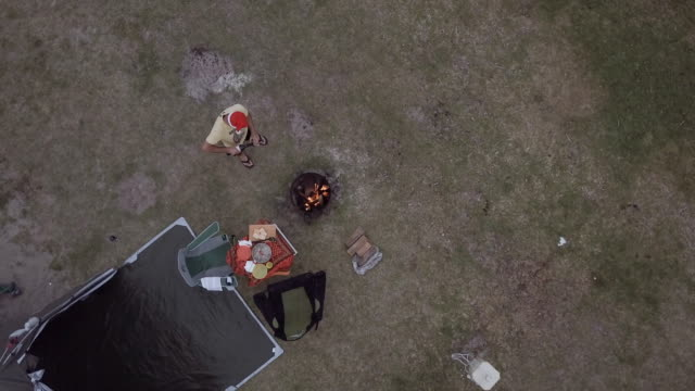 4K Eye's bird view of a man camping, with a fire and celebrating Christmas, Victoria, Australia