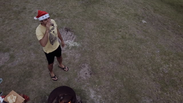 4k eye's bird view of a man camping, with a fire and celebrating christmas, victoria, australia - flip flop stock videos and b-roll footage