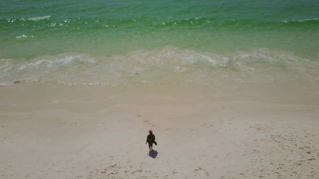 4K Eye's Bird view of a woman walking at the shore of a beach, Jervis Bay, Australia