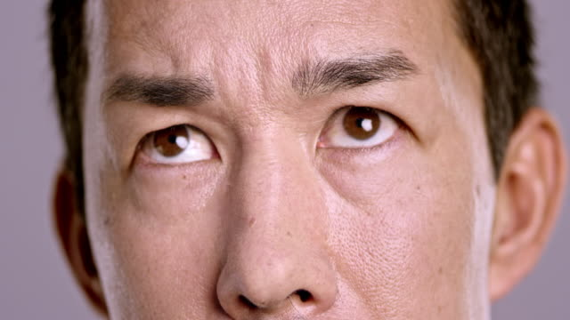 eyes of a scared asian man - confusion stock videos & royalty-free footage