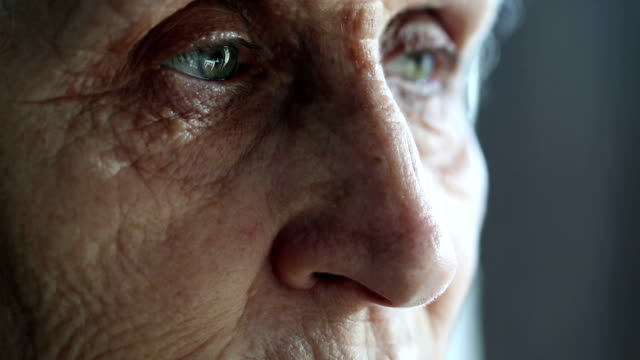 Eyes of a senior woman turning to the camera while looking away