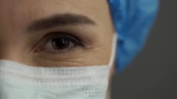 eyes of a smiling nurse or doctor in a surgical mask