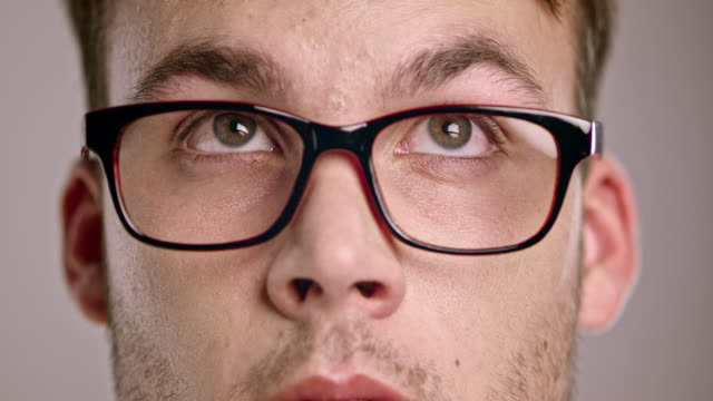 eyes of a young caucasian man wearing eyeglasses looking around - eyeglasses stock videos & royalty-free footage