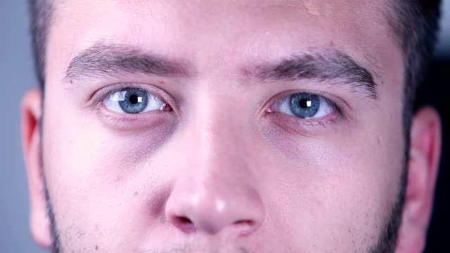 eyes of a young man looking at camera - blinking stock videos & royalty-free footage