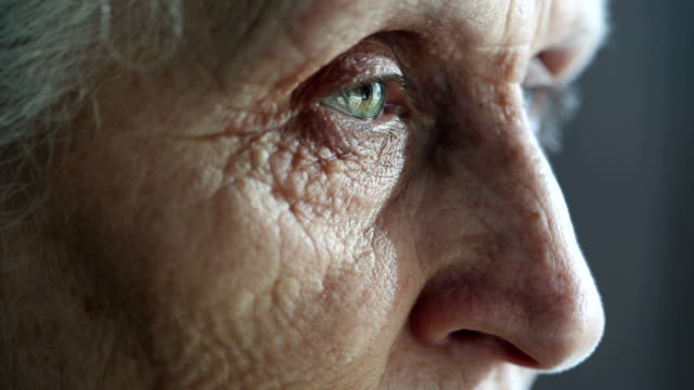 eyes of an old woman looking away in concentration - senior women stock videos & royalty-free footage
