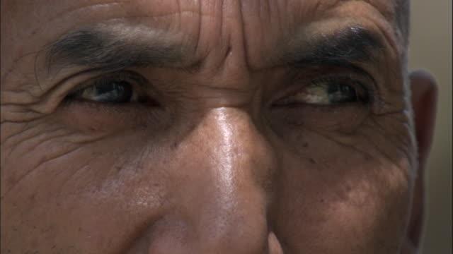 vídeos de stock, filmes e b-roll de eyes of man, hetian, xinjiang province, china, - olhando ao redor