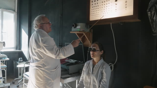 eyesight testing with a phoropter and an eye chart. young woman examining eyes at ophthalmologist. white collar workers. active seniors at their work place. - lens optical instrument stock videos & royalty-free footage