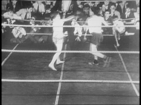ezra stone pushes through boys crowded around boxing ring climbs through ropes / two young boys in shorts box in ring / boy in toboggan cap blows... - anno 1941 video stock e b–roll