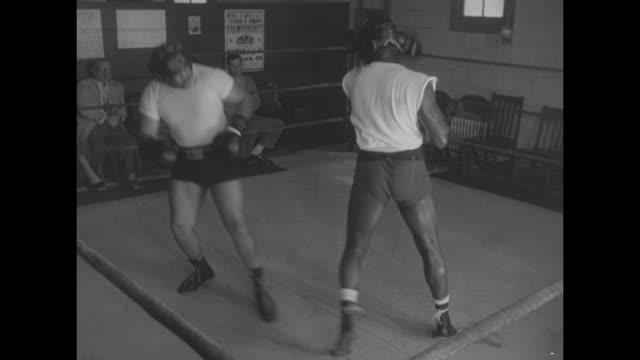 Ezzard Charles works out on speed bag / VS sparring with men and women seated at ringside / VS Walcott dancing and punching footwork / VS working out...