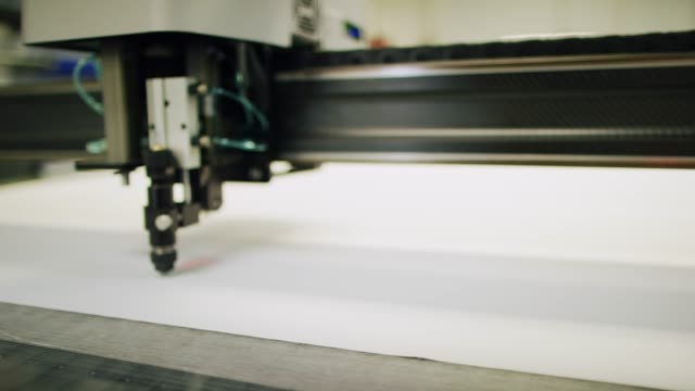 a cnc fabric cutting machine cuts fabric in an indoor manufacturing facility - atelier fashion stock videos & royalty-free footage