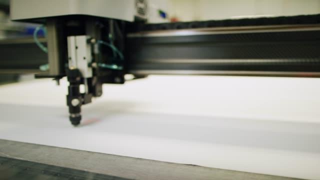 vídeos de stock e filmes b-roll de a cnc fabric cutting machine cuts fabric in an indoor manufacturing facility - indústria têxtil