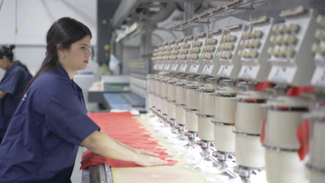 fabric operator lining down the fabrics to be embroidered - textile industry stock videos & royalty-free footage