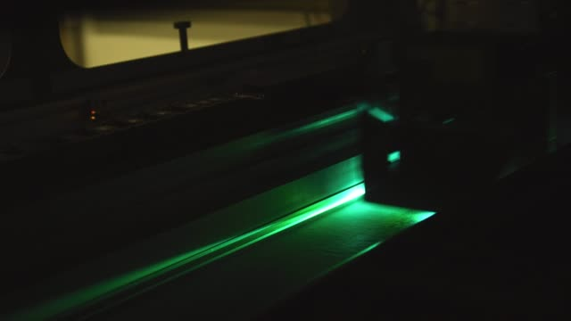 vídeos de stock e filmes b-roll de a cnc fabric printer machine prints on fabric in an indoor manufacturing facility - indústria têxtil