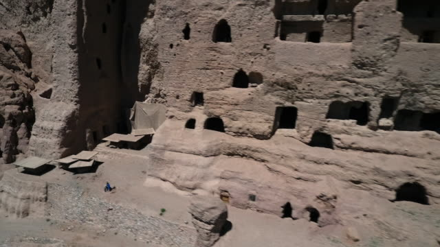 facade of cliffside  ruins with openings, holes and caverns. - lehm mineral stock-videos und b-roll-filmmaterial