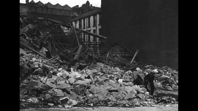 Facade of fireblackened building with man looking out of window in World War II London / view of destruction seen from windows and doorway of wrecked...