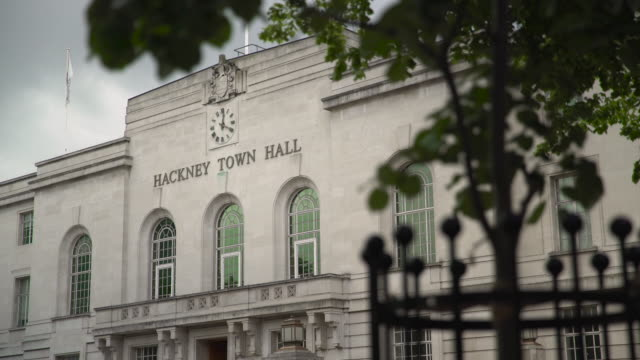 facade of hackney town hall framed by tree - local government building stock videos & royalty-free footage