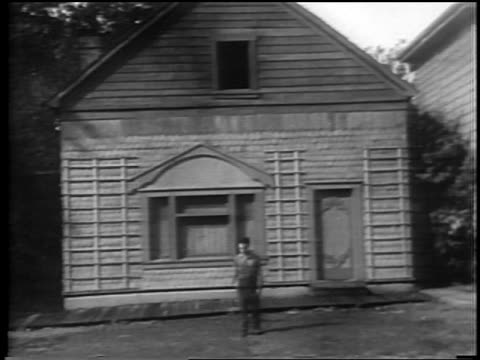 vidéos et rushes de b/w 1928 facade of house falling onto man leaves him unharmed / feature - acteur