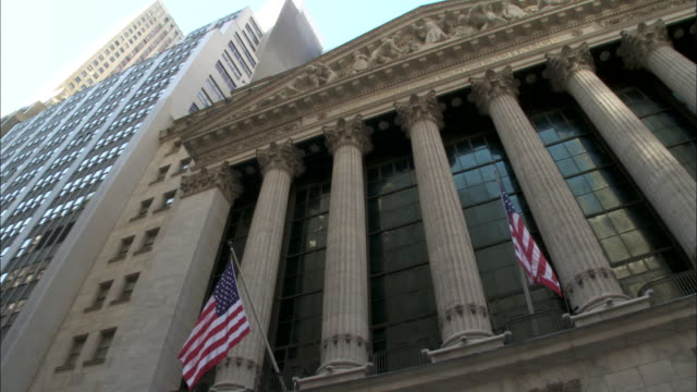 Facade of NY Stock Exchange building columns pediment sculptures US flags on Wall Street in Lower Manhattan NYC Financial District downtown Occupy...