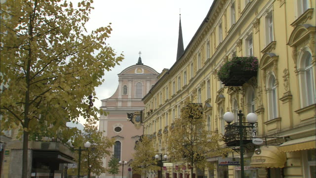 facade of parish church at end of tree-lined street, bad ischl, austria - オーストリア点の映像素材/bロール