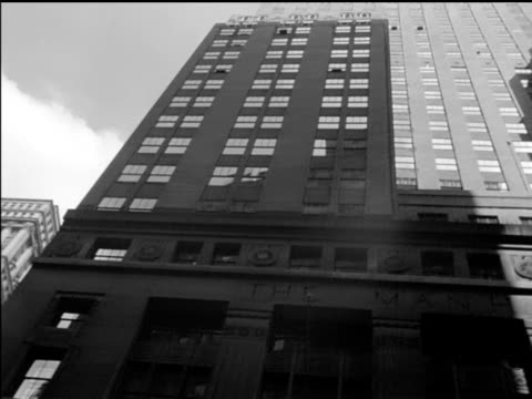 / facade of skyscraper on wall street / la pan of skyscraper tilt up facade of business buildings many windows / several people strolling along... - narrow stock videos & royalty-free footage