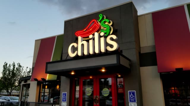 facade with sign at dusk at chili's restaurant in dublin california april 16 2018 - chilli con carne video stock e b–roll
