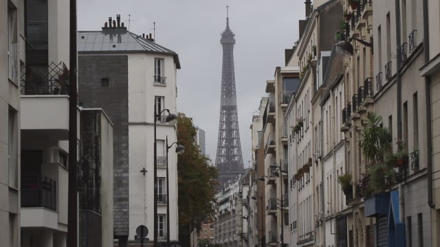 facades of buildings in paris with the eiffel tower in the background - house rental stock videos & royalty-free footage