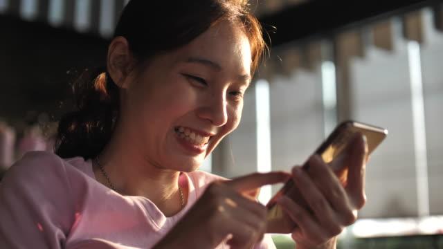 vídeos de stock, filmes e b-roll de enfrente mulher asiática usando telefone inteligente em cafeteria - portable information device